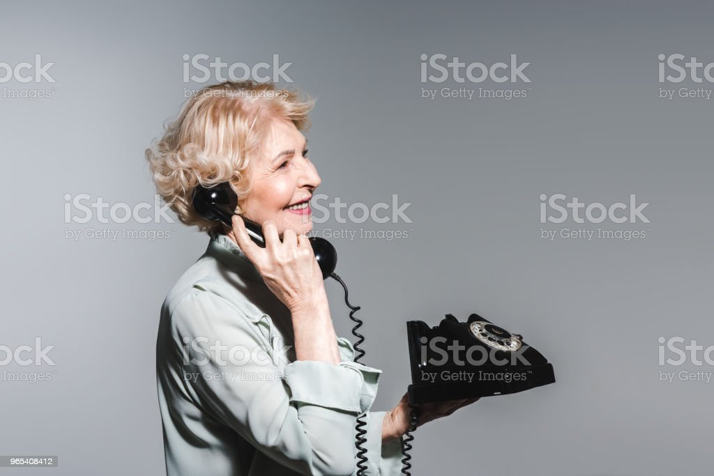 side view of smiling senior woman talking by vintage phone isolated on grey royalty-free stock photo