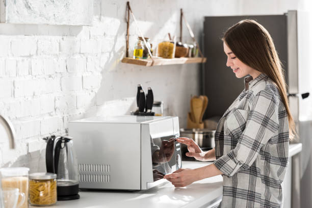 side view of smiling woman in shirt using microwave in kitchen stock photo