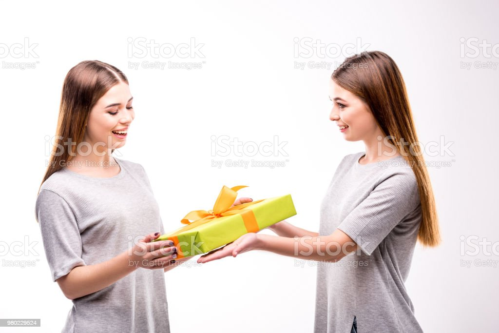 Side View Of Smiling Woman Presenting Wrapped Gift To Twin Sister Royalty Free Stock Photo