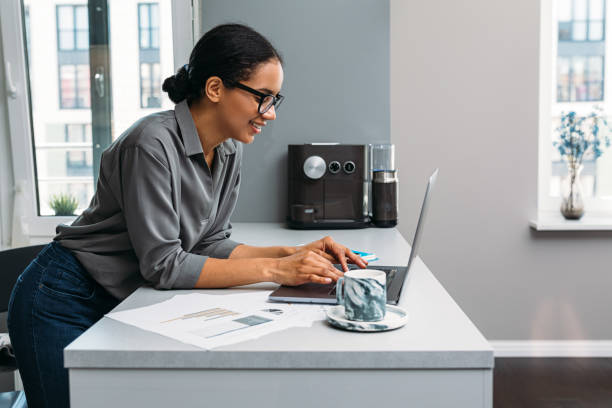Side view of smiling woman working with laptop on kitchen counter at home stock photo