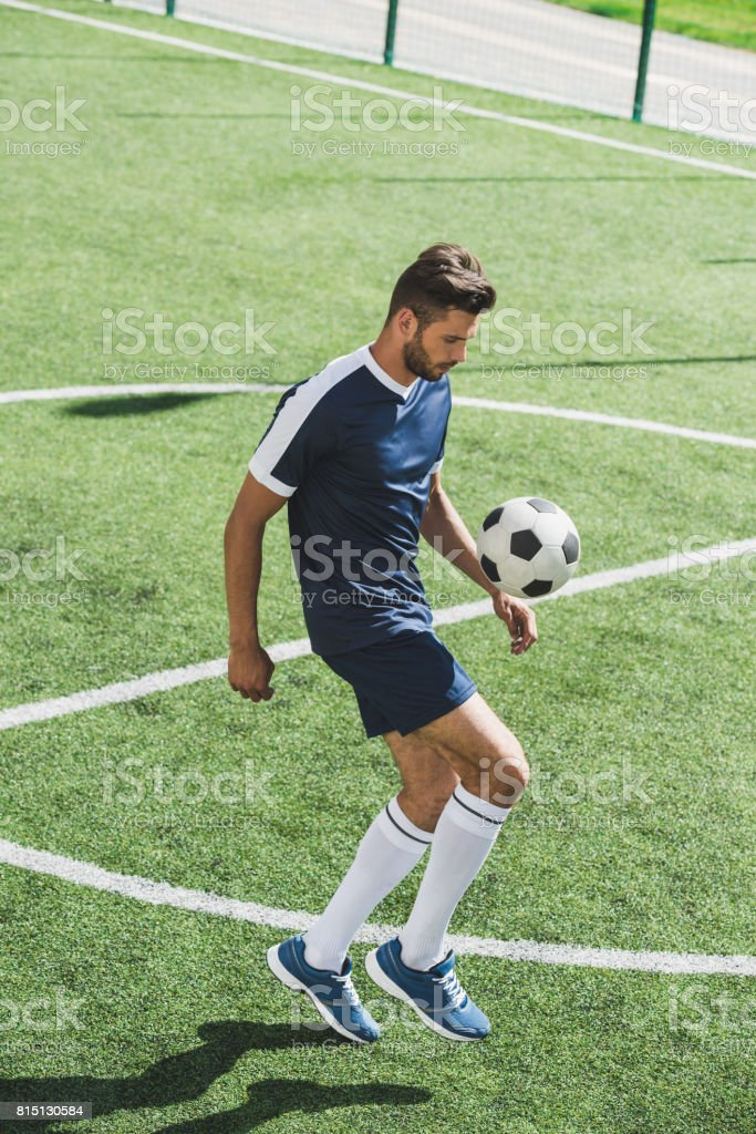 side view of soccer player kicking ball while training on soccer pitch