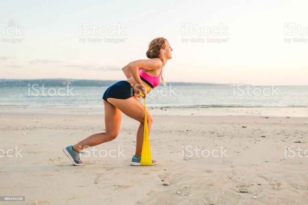 side view of sportswoman doing exercise with stretching band on beach - Zbiór zdjęć royalty-free (Aktywny tryb życia)