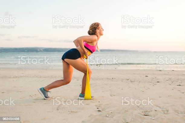 Widok Z Boku Sportsmenki Wykonującej Ćwiczenia Z Rozciągającą Opaską Na Plaży - zdjęcia stockowe i więcej obrazów Pchnięcie z wypadem