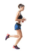 istock Side view of sporty athletic female jogger jogging and looking down 854374282