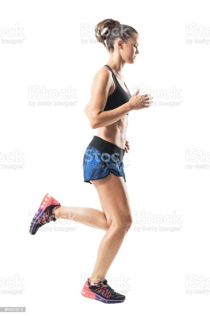 Side view of sporty female athlete running and looking down. stock photo