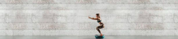 Side view of sporty woman doing exercises on bosu ball. In background gray wall, copy space. stock photo