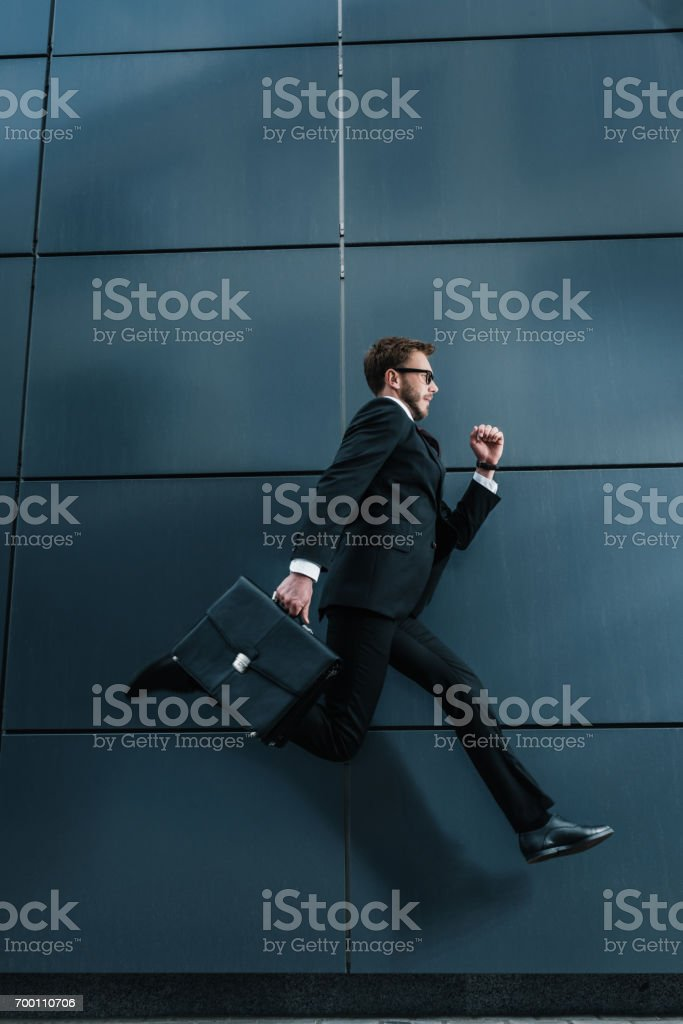 Side view of stylish businessman with briefcase running and jumping stock photo