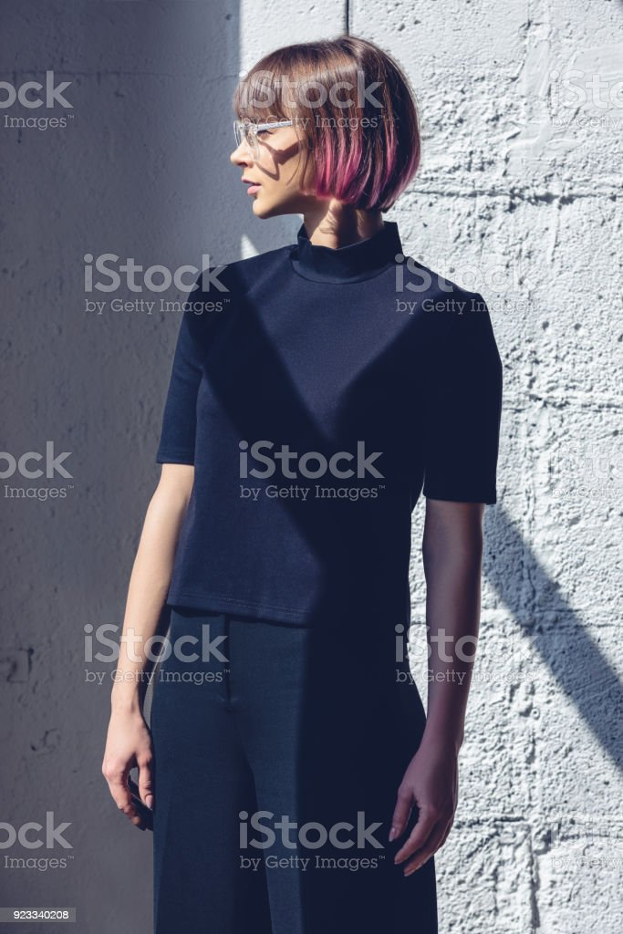 a5beef573 Side View Of Stylish Girl In Black Clothes Standing Near Wall Stock ...