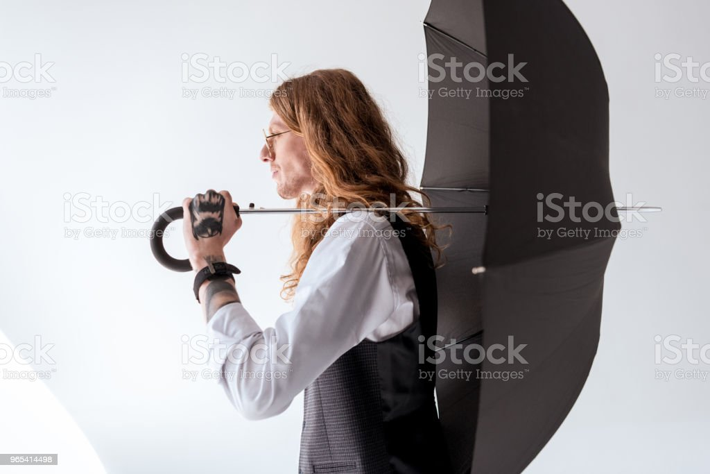 side view of stylish tattooed businessman with curly hair holding black umbrella zbiór zdjęć royalty-free
