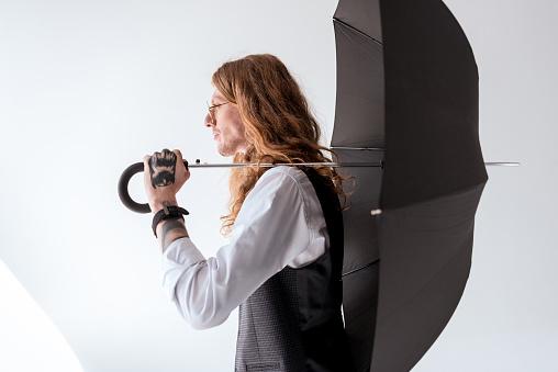 곱슬 머리에 검은 우산을 들고 세련 된 문신된 사업가의 측면 보기 개인 장식품에 대한 스톡 사진 및 기타 이미지