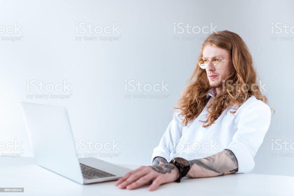 Side View Of Stylish Tattooed Businessman With Curly Hair Looking At Laptop - zdjęcia stockowe i więcej obrazów Biuro