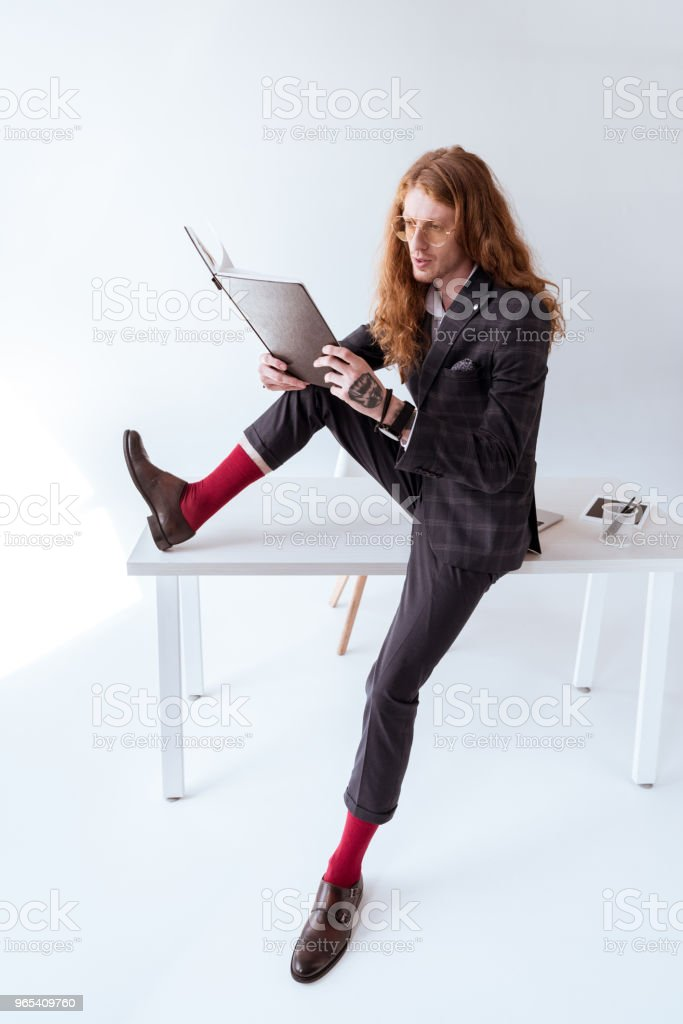 side view of stylish tattooed businessman with curly hair sitting on table and reading documents zbiór zdjęć royalty-free