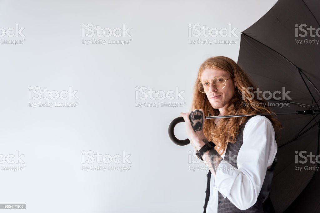 side view of stylish tattooed businessman with ginger hair holding black umbrella isolated on white zbiór zdjęć royalty-free