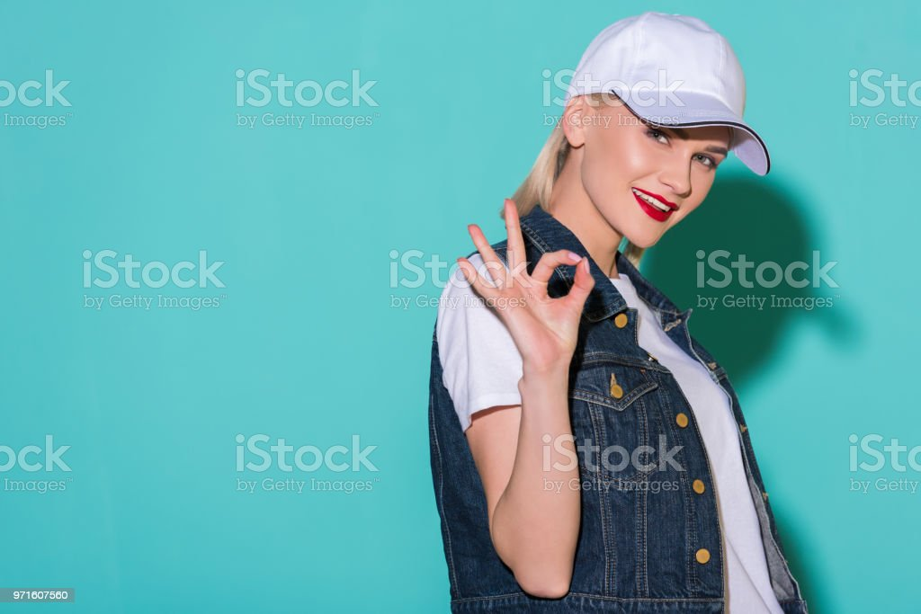 Side View Of Stylish Young Woman In White Shirt Cap And Denim Jacket