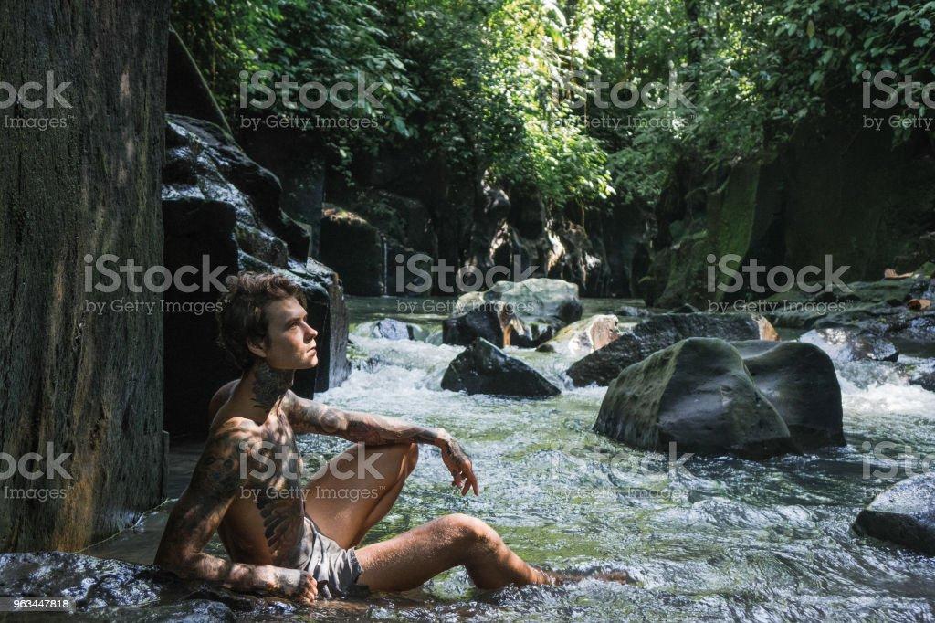 dövmeli adam buzlu su ve yeşil bitkiler etrafında, bali, Endonezya ile dinlenme yan görünüm - Royalty-free Adamlar Stok görsel