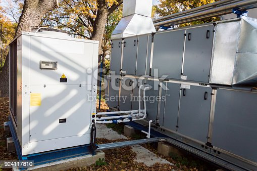 istock Side view of the gray commercial central air handling unit with cooling coil and big condensing unit standing outdoor on the ground covered by fallen leaves 924117810