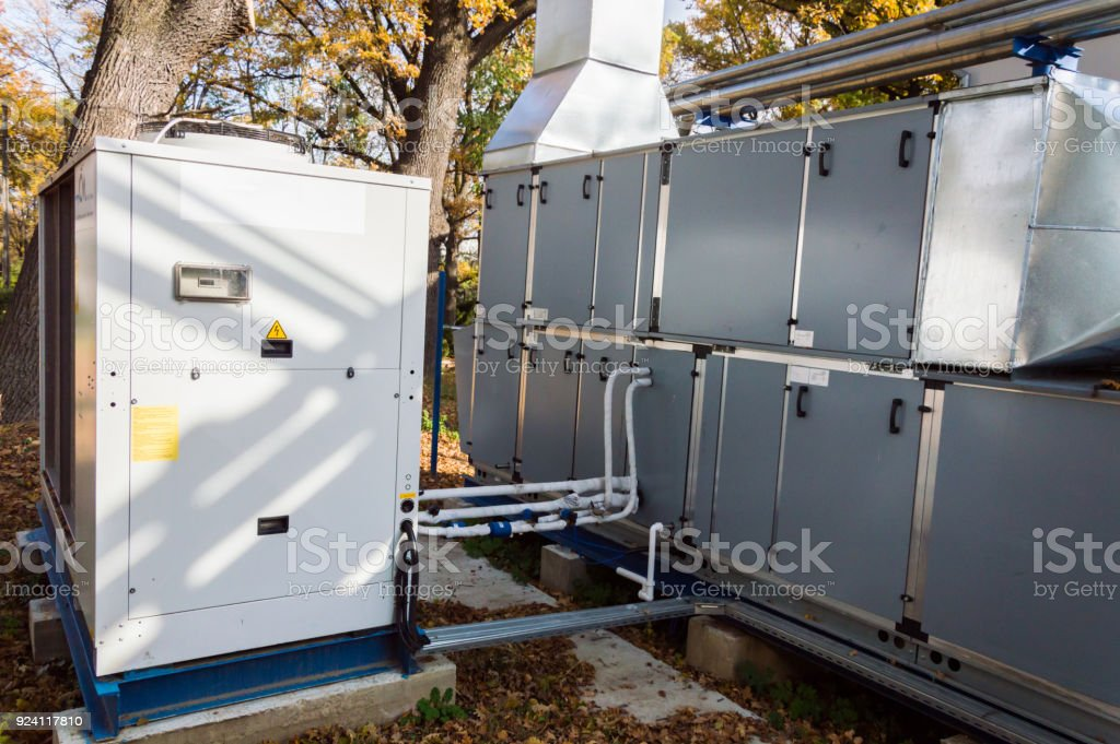 Side view of the gray commercial central air handling unit with cooling coil and big condensing unit standing outdoor on the ground covered by fallen leaves stock photo