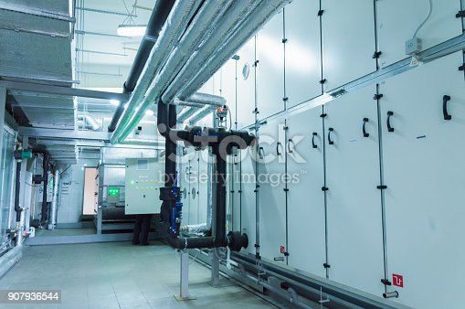 istock Side view of the huge gray industrial air handling unit in the ventilation plant room 907936544