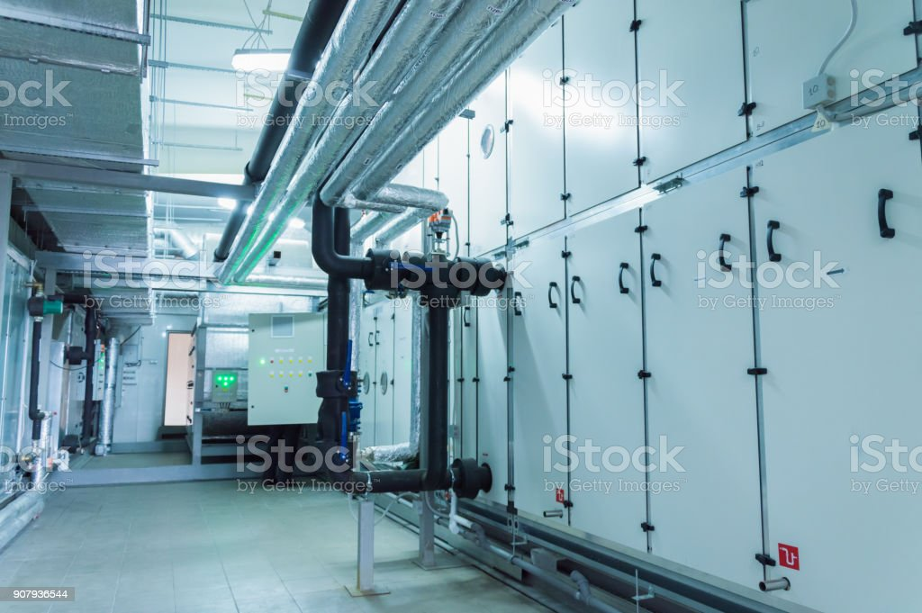 Side view of the huge gray industrial air handling unit in the ventilation plant room stock photo