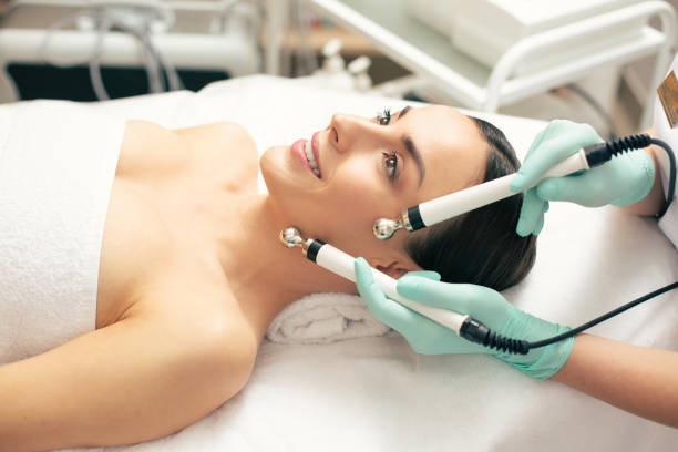 Side view of the smiling lady undergoing modern microcurrent therapy stock photo