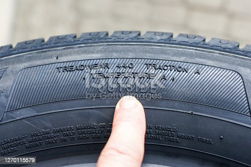 Side view of new tire with tire traction rating, treadwear index and tire outside designation