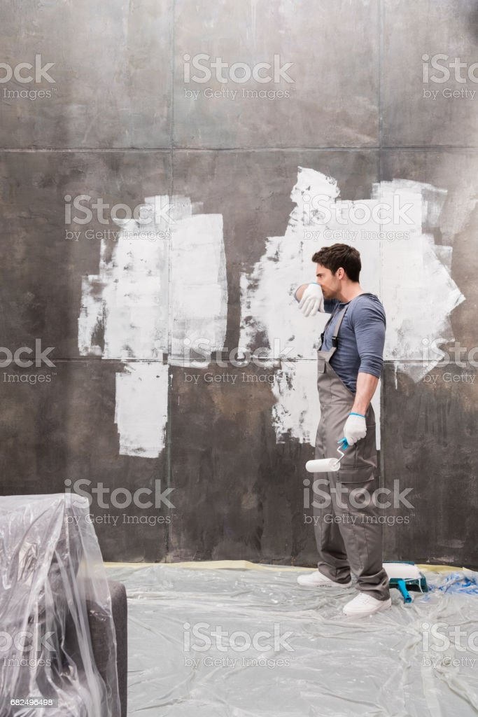side view of tired young man with paint roller renovating home photo libre de droits