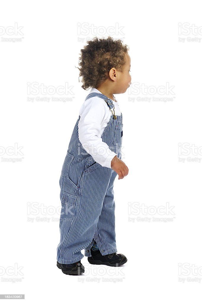 Side View Of Toddler In Classic Dungarees Stsnding stock photo