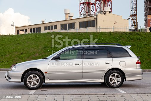 Novosibirsk, Russia - 11.06.20: Side view of Toyota Caldina car of 2000 release in the back of a silver T210 station wagon in a parking lot with a green lawn.