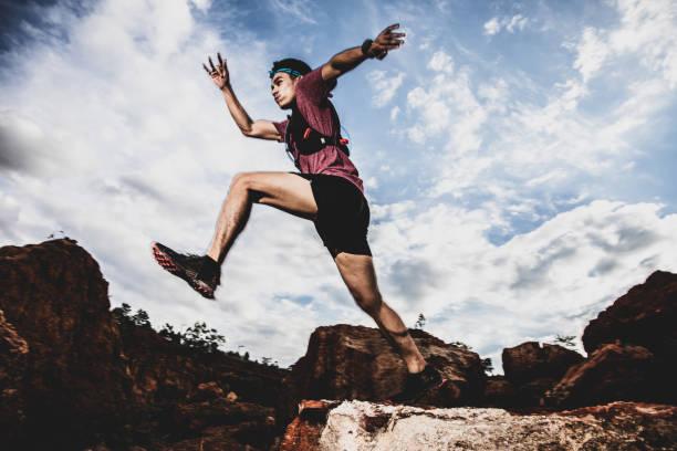 sidovy av trail runner hoppar på horisonten och sten - jogging hill bildbanksfoton och bilder
