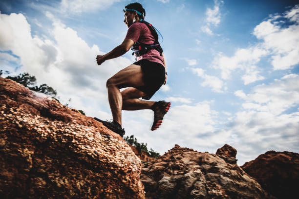 side view of trail runner jumping on the horizon and stone