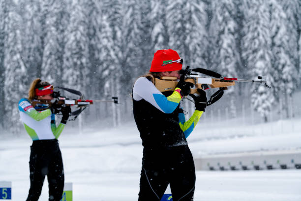 Seitenansicht der beiden Athletinnen üben Zielschießen im Schneesturm – Foto