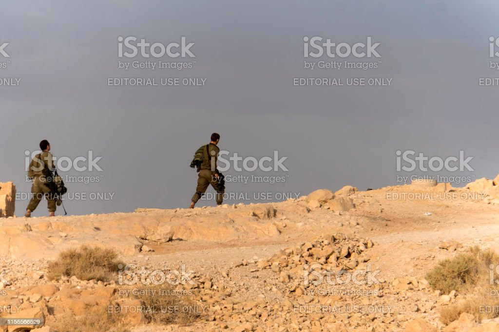 Side view of two infantry men with weapons in walking in desert in...