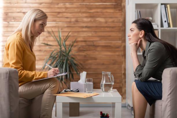 Seitenansicht zweier hübscher Frauen, die im Beratungsraum sprechen – Foto