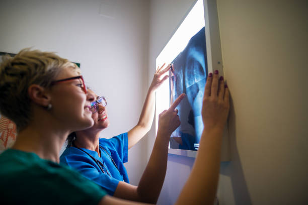side view of two professional nurses checking x-ray in a doctors office. - macchina per radiografie foto e immagini stock