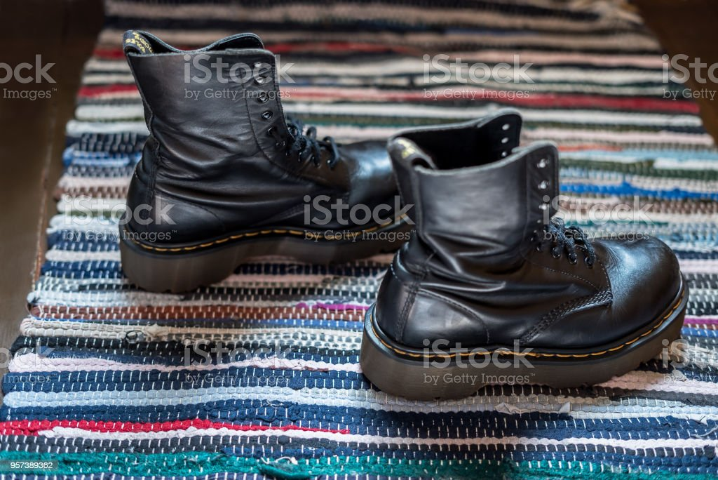 Side view of two robust, black ankle leather boots on a colorful rug stock photo