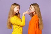 カラフルな cl で2人の若いブロンド双子姉妹の女の子の側面図