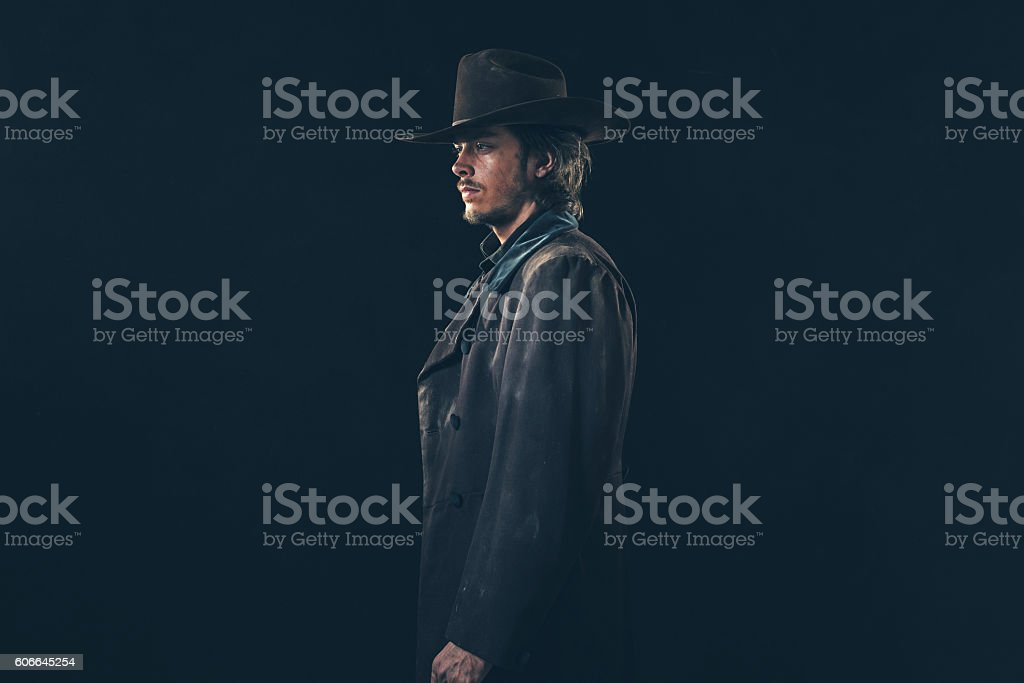 Side view of vintage 1900 cowboy. Young man. Studio shot. stock photo