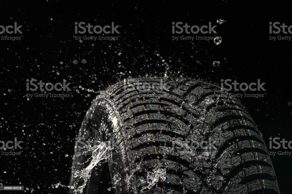 Seitenansicht des Spritzwasser auf neuen symmetrischen Reifen – Foto