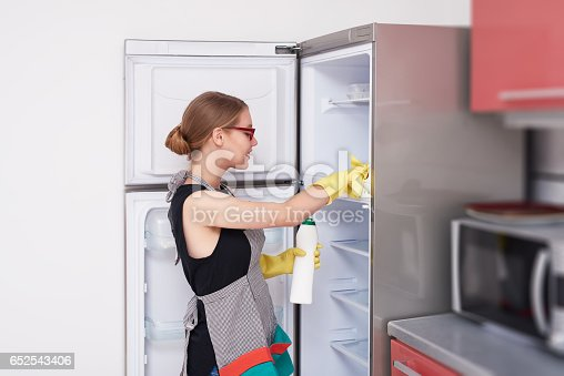 lifestyle shot of young woman cleaning the fridge with solution, wearing protective glove.