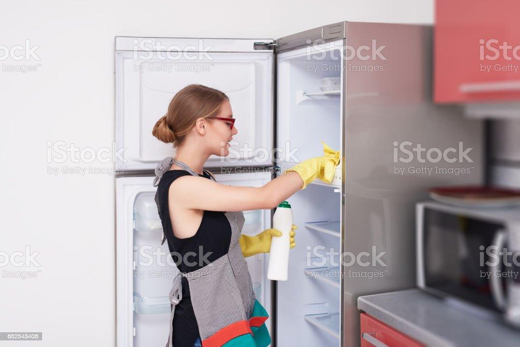 Seitenansicht der Frau den Kühlschrank reinigen – Foto