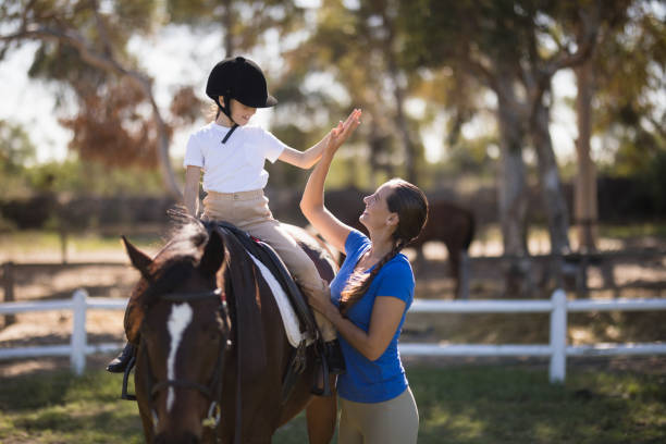 Side view of woman giving high five to girl sitting on horse picture id837983142?b=1&k=6&m=837983142&s=612x612&w=0&h=5ox5puzs6ld yab1plre3dkrelx1nrp94seypyobe9o=