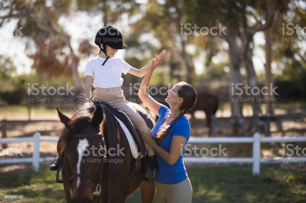Side view of woman giving high five to girl sitting on horse stock photo