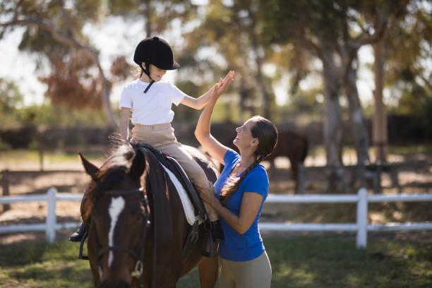 馬に座っている女の子にハイファイブを与える女性の側面図 - 乗馬 ストックフォトと画像