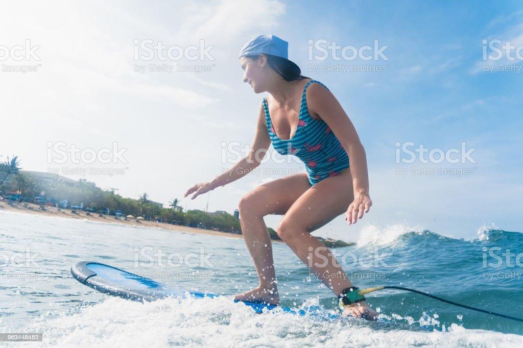 widok z boku kobiety w czapce i kostiumie kąpielowym surfing w oceanie - Zbiór zdjęć royalty-free (Bali)