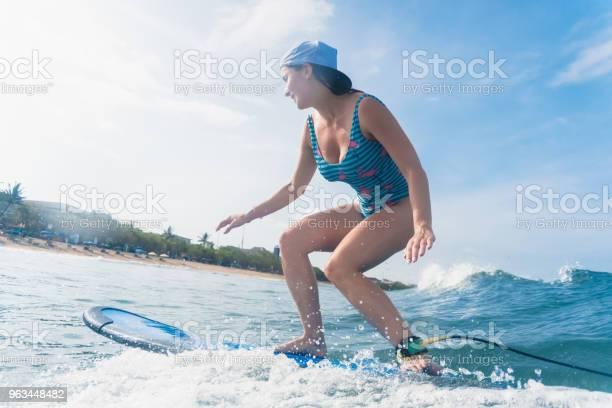 Widok Z Boku Kobiety W Czapce I Kostiumie Kąpielowym Surfing W Oceanie - zdjęcia stockowe i więcej obrazów Bali