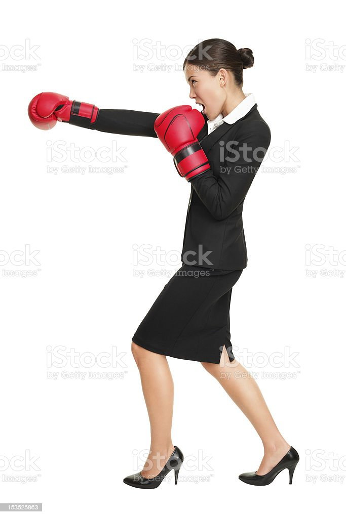 Side view of woman in suit punching with red boxing gloves royalty-free stock photo