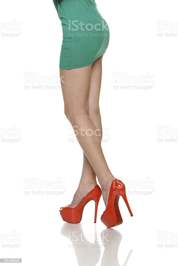 Side view of woman legs in green mini skirt royalty-free stock photo