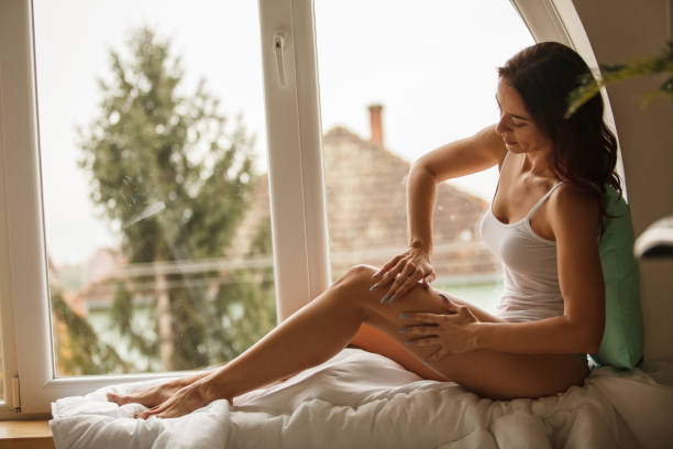 Side view of woman massaging her legs while relaxing stock photo