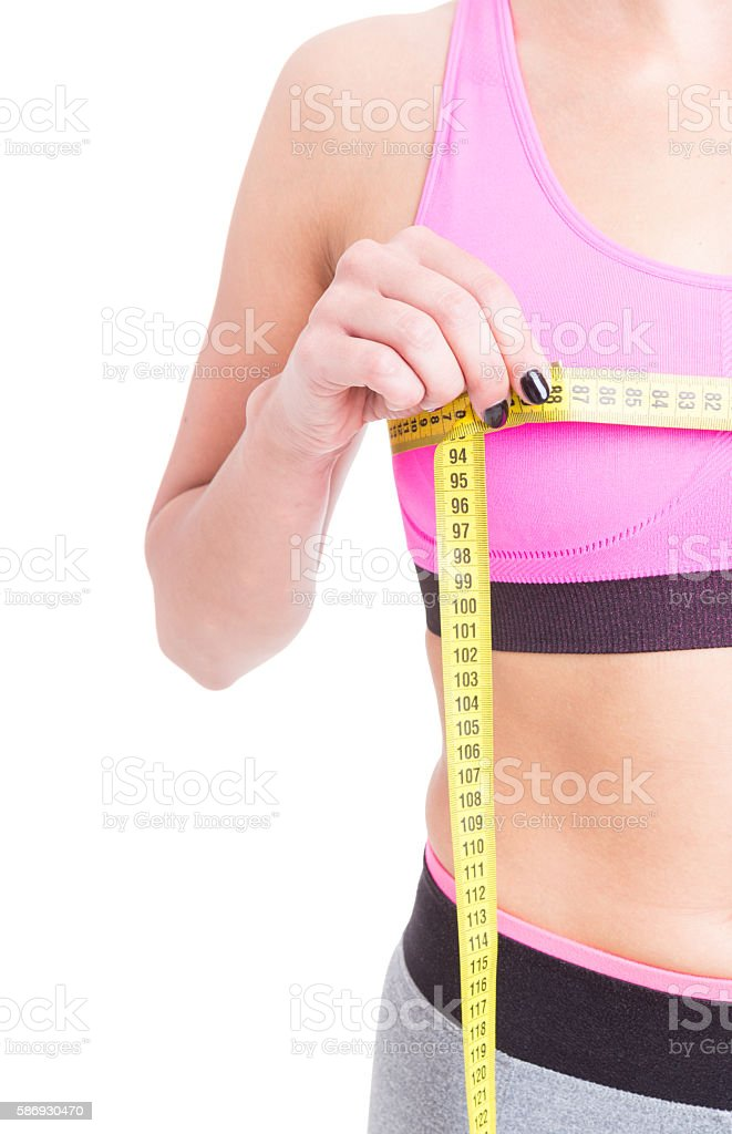 Side view of woman measuring her bust line stock photo