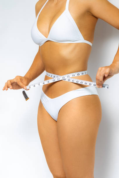 Side view of woman measuring waist with measure band. stock photo